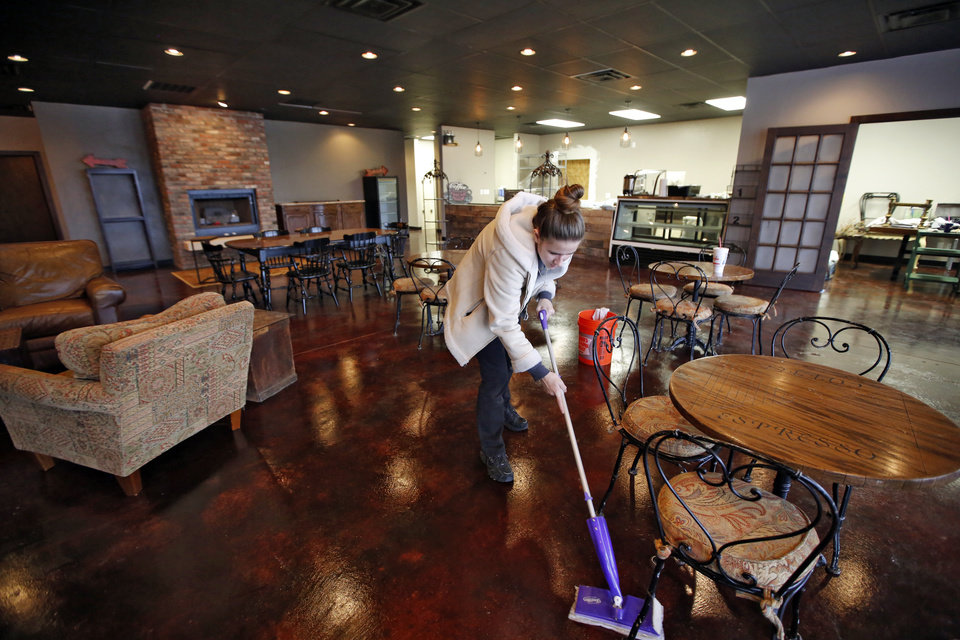 Photo -  Whitney Hanson mops the floor in preparation for the opening of the Higher Grounds Coffee Shoppe and Bakery, 5814 NW 63. [Photo By Steve Gooch, The Oklahoman]