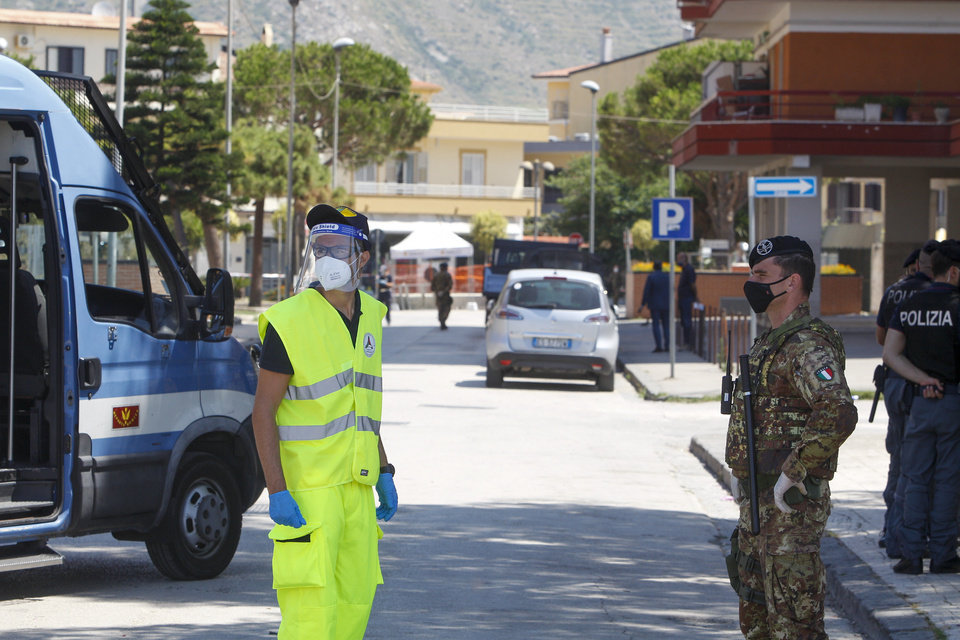 Photo -  Civil protection and army officers stand at a road block in front of an apartment complex where dozens of COVID-19 cases have been registered among a community of Bulgarian farm workers, in Mondragone, in the southern Italian region of Campania, Friday, June 26, 2020. The governor of the region is insisting that the farm workers should stay inside for 15 days, not even emerging for food, and that the national civil protection agency should deliver them groceries. (AP Photo/Riccardo De Luca)
