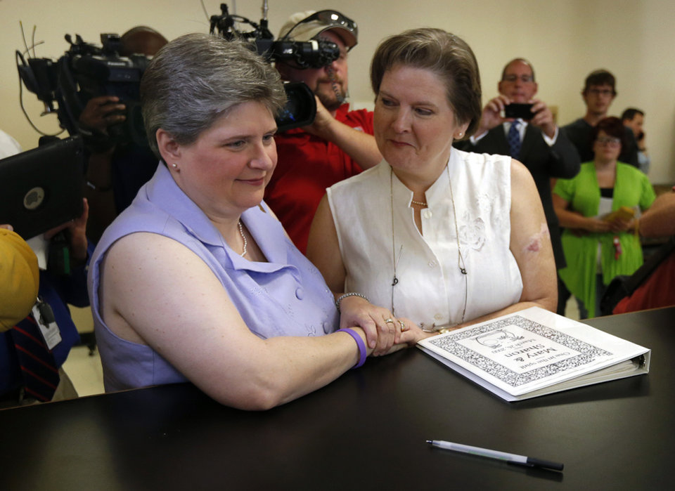 Photo - Sharon Baldwin (left) and Mary Bishop (right), two Tulsa women at the center of a gay marriage case that was appealed to the Supreme Court, apply for a marriage license on Monday, October 6, 2014 at the Tulsa County Courthouse in Tulsa, Okla. MATT BARNARD/Tulsa World