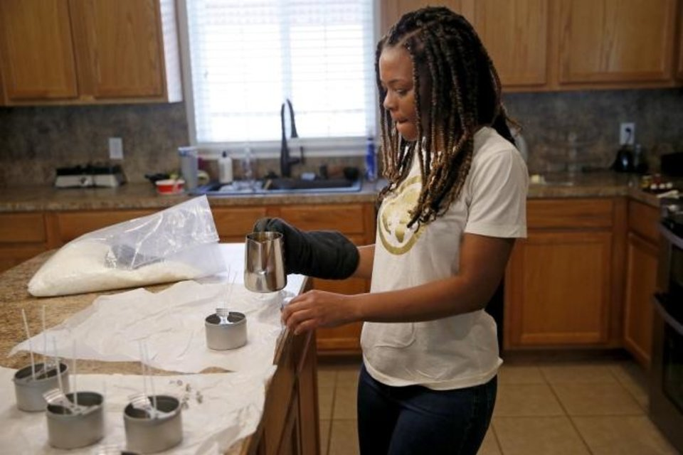 Photo -  Candice Jackson, owner of Speak Life Candle Company & More, makes candles on June 16 in Oklahoma City. She is one of the roster of Black artists, vendors and performers participating in the rescheduled