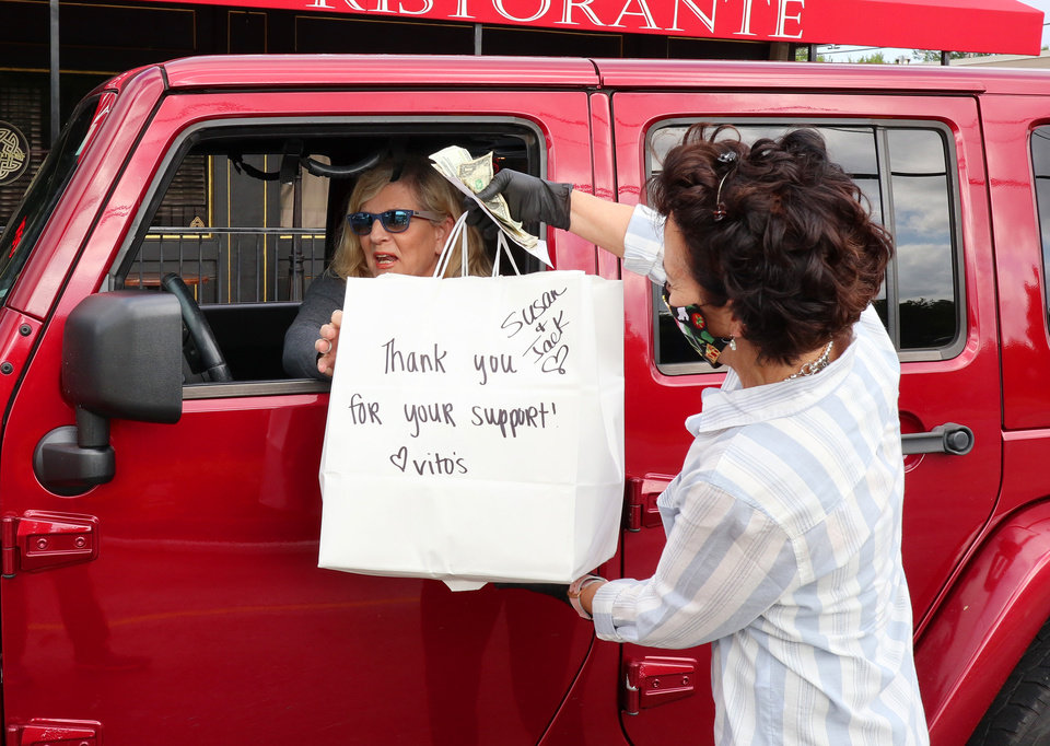 Photo - Owner Cathy Cummings delivers a carry out order to Susan McCann and her grandson, Jack. Vito's Ristorante will continue to have carry out even after the dining room opens because of the limits in the number of customers allowed to dine in at once. Wednesday, May 13, 2020. [Doug Hoke/The Oklahoman]