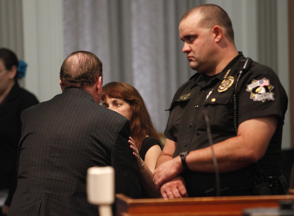 Photo - Jerome Ersland, left talks with an unidentified women before his guilty verdict was read in Oklahoma City, Oklahoma , Thursday, May 26, 2011. Photo by Steve Gooch, Pool/ The Oklahoman