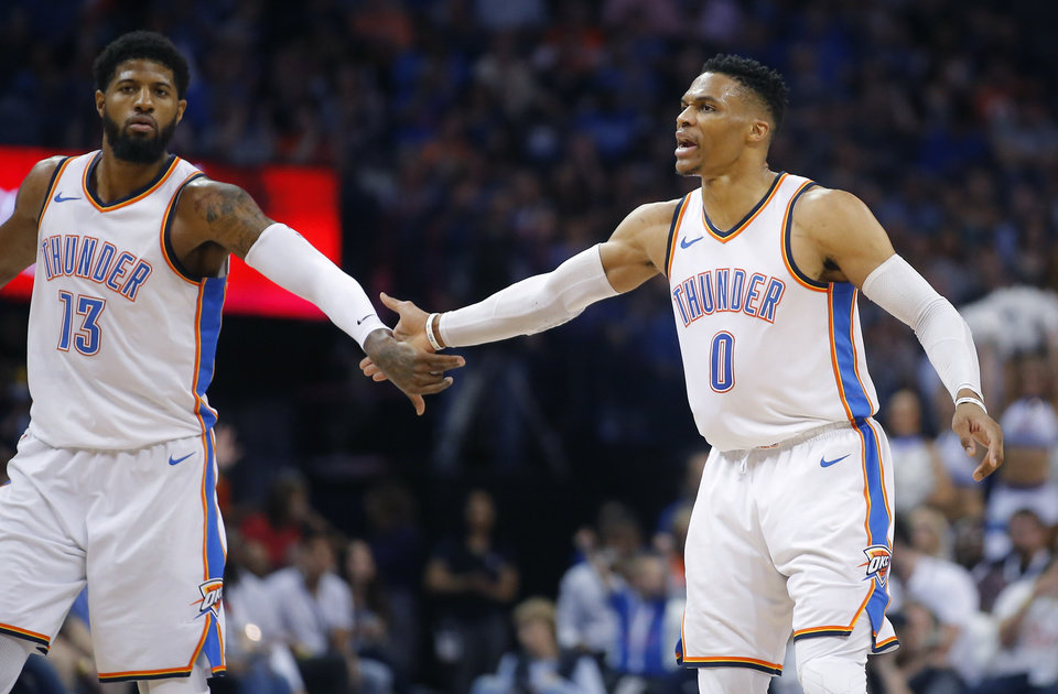 Photo - Oklahoma City's Russell Westbrook (0) slaps hands with Paul George (13) during an NBA basketball game between the Oklahoma City Thunder and the Memphis Grizzlies at Chesapeake Energy Arena in Oklahoma City, Wednesday, April 11, 2018. Photo by Bryan Terry, The Oklahoman