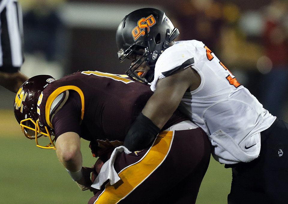 Photo - Oklahoma State's Emmanuel Ogbah (38) sacks Central Michigan's Cooper Rush (10) during the college football game between the Central Michigan Chippewas and the Oklahoma State University Cowboys at the Kelly/Shorts Stadium in Mount Pleasant, Mich., Thursday, Sept. 3, 2015. Photo by Sarah Phipps, The Oklahoman