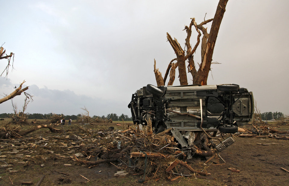 Photo - The car owned by Tom Chronister is impaled on a tree after being destroyed by a tornado that hit north of El Reno, Tuesday, May 24, 2011. Photo by Chris Landsberger, The Oklahoman ORG XMIT: KOD