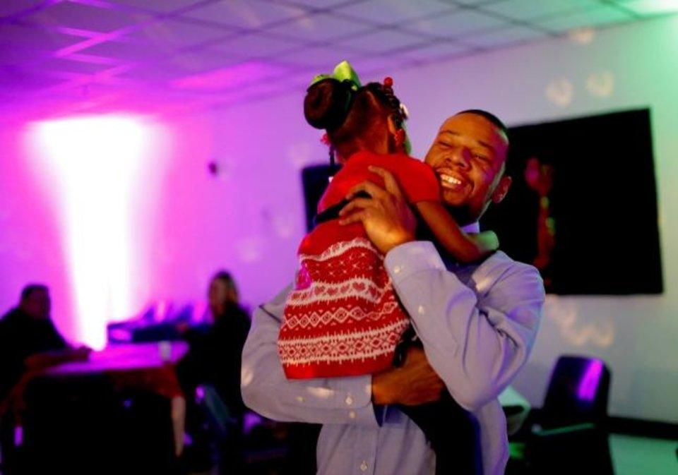 Photo -  Mark Warner laughs as he twirls his daughter around during a Daddy-Daughter Social at Oklahoma City Transitional Living Center, a private community correctional center in Oklahoma City. [Sarah Phipps/The Oklahoman]