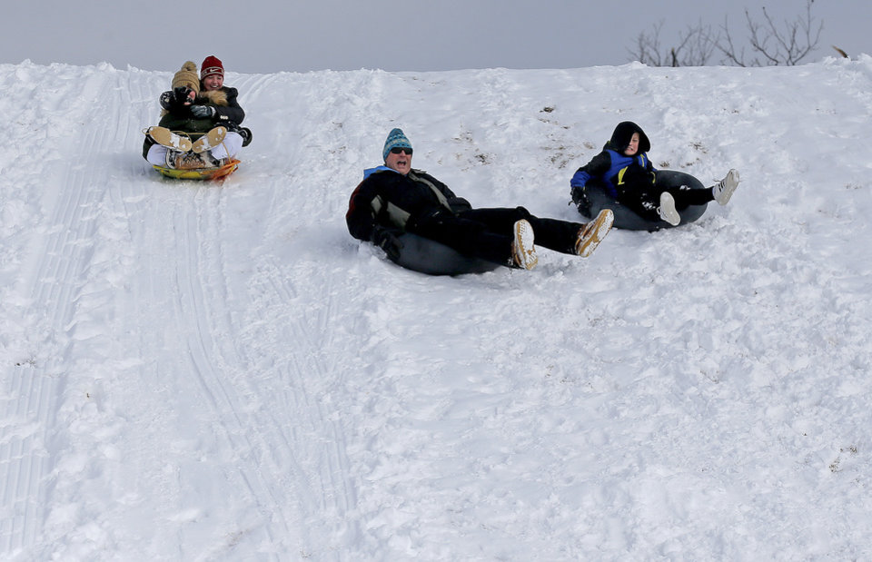 Photo - From left to right: Layne Patterson, Farrah Enright, Kevin Enright and Jace Enright sled on a hill along Hefner Road in Oklahoma City, Wednesday, Feb. 17, 2021. [Sarah Phipps/The Oklahoman]