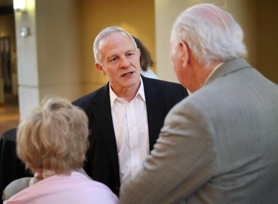 Photo -  Artist Mike Wimmer speaks with attendees during a reception for his portrait exhibit