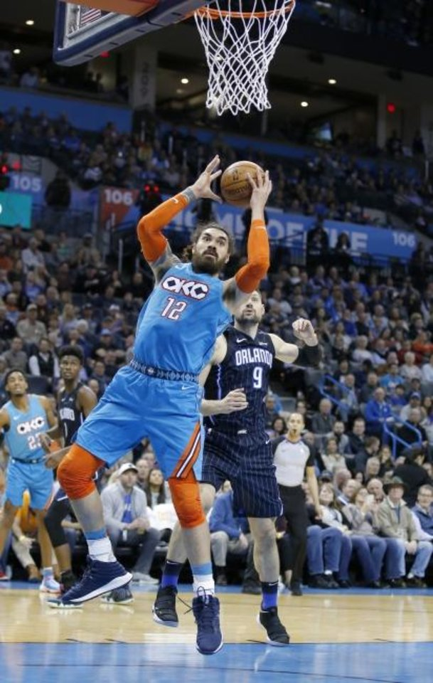 Photo -  Oklahoma City's Steven Adams goes up for a basket in front of Orlando's Nikola Vucevic during Tuesday night's game at Chesapeake Energy Arena. [SARAH PHIPPS/THE OKLAHOMAN]