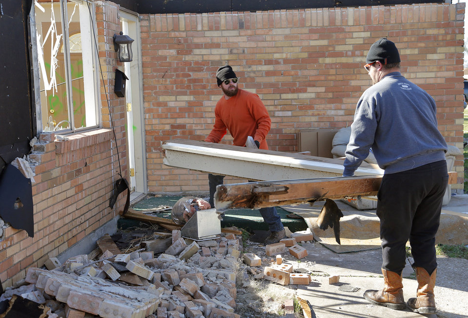 Photo - Josh Bennitt, left, and Chase Farmer clean up storm damage to a home in Moore, Okla. on Thursday, March 26, 2015. A tornado hit the area on Wednesday evening causing damage in the area.  Photo by Chris Landsberger, The Oklahoman