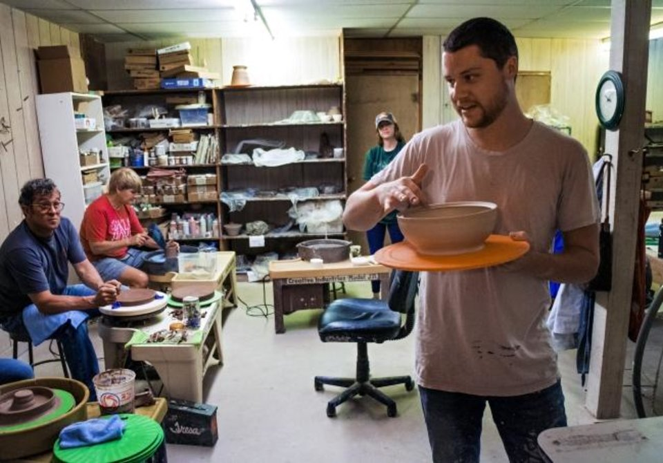 Photo -  Taylor Dickerson offers instruction to students in his pottery class at The House of Clay in Oklahoma City.   [Chris Landsberger/The Oklahoman]