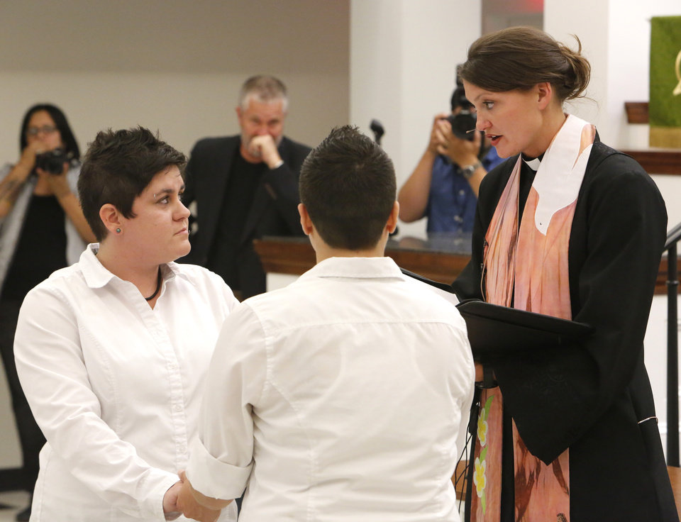 Photo - Same-sex marriages. Lauren Tidwell and Sara Yarbrough say their marriage vows with Rev. Lori Walke at Mayflower Congregational Church, 3901 NW 63, Monday, October 6, 2014. Photo by David McDaniel