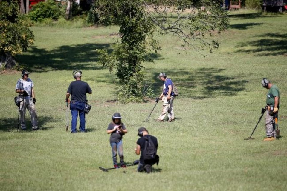 Photo - A group metal detector enthusiasts walk across a field while metal detecting in Fallis, Okla., Saturday, Sept. 14, 2019. [Bryan Terry/The Oklahoman]