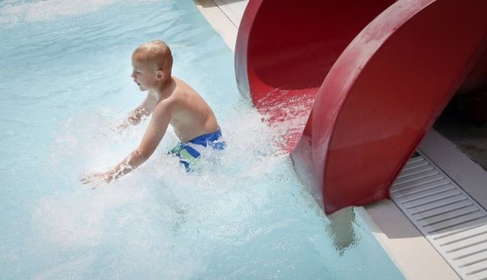 Photo -  Braedon Conrad, 8, lands in the pool at the bottom of a water slide Saturday at Will Rogers Family Aquatic Center.