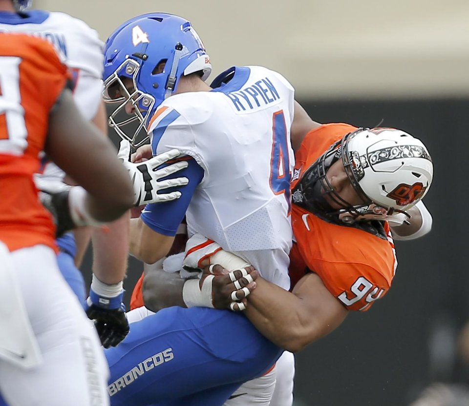 Photo -  Oklahoma State's Jordan Brailford brings down Boise State's Brett Rypien for one of his two sacks Saturday. [Photo by Bryan Terry, The Oklahoman]