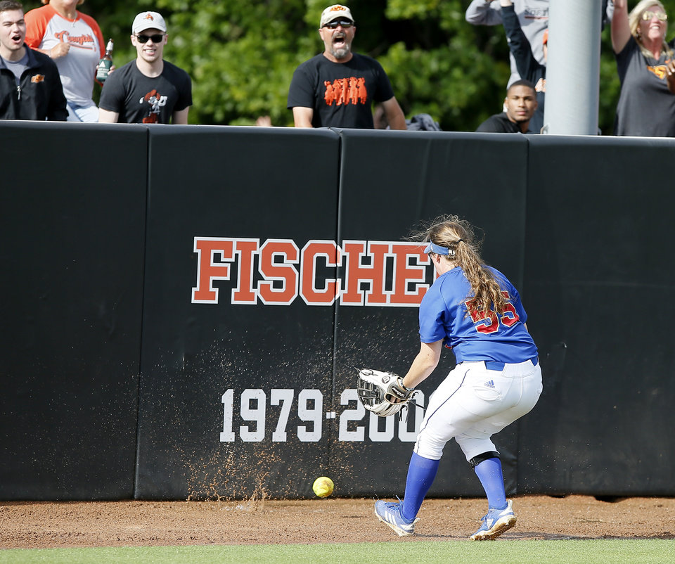 Photo - The ball splashes in mud in front of Tulsa's Julia Hollingsworth (55) as Oklahoma State scores a run in the third inning of the Stillwater Regional NCAA softball tournament game between Oklahoma State University (OSU) and Tulsa in Stillwater, Okla., Saturday, May 18, 2019. Oklahoma State won 2-1. [Bryan Terry/The Oklahoman]