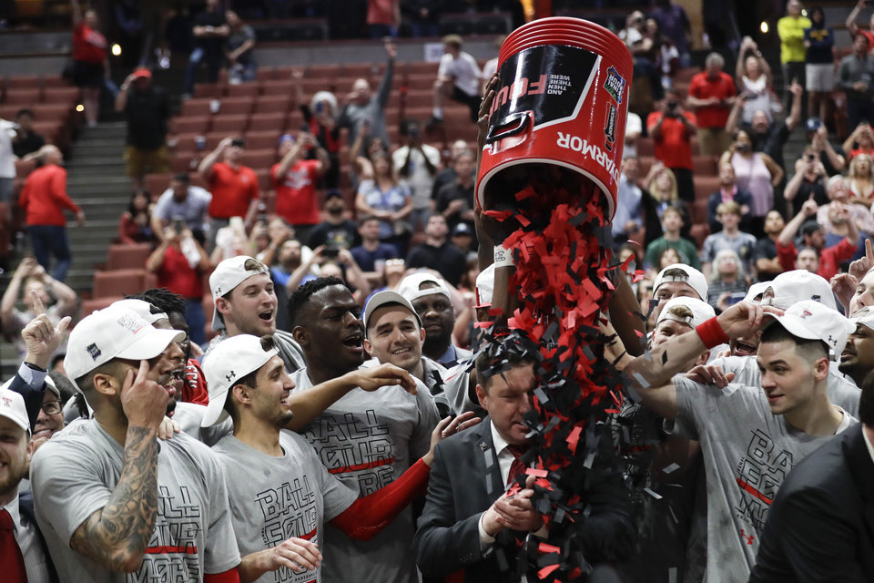 Photo - Texas Tech players shower coach Chris Beard with confetti after their win against Gonzaga during the West Regional final in the NCAA men's college basketball tournament Saturday, March 30, 2019, in Anaheim, Calif. Texas Tech won 75-69. (AP Photo/Marcio Jose Sanchez)