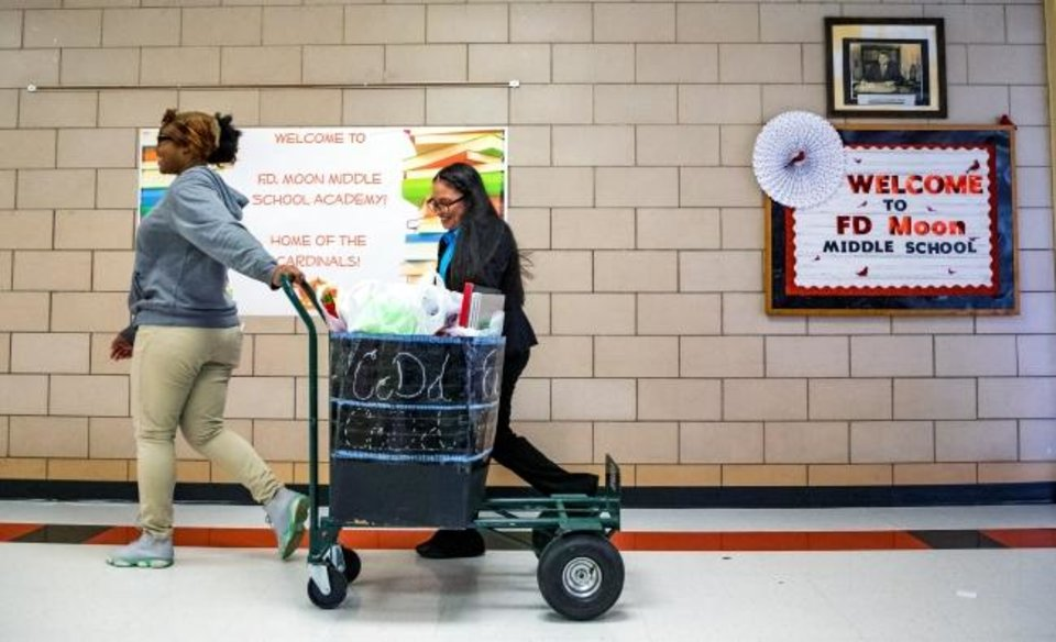 Photo -  Students Kalia Long, left, and Evelin Ramirez help bring in school supplies from a $12,000 donation to F.D. Moon Middle School in Oklahoma City from nonprofit Generation Why on Wednesday.  [Chris Landsberger/The Oklahoman]
