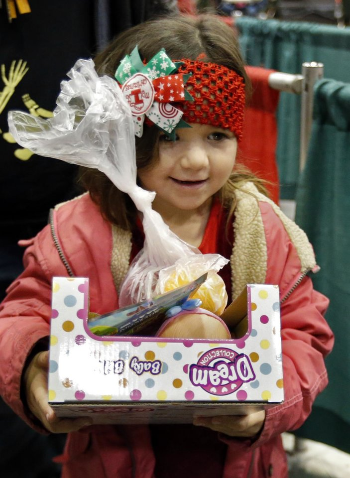 Photo - Lauri Williams, 3, carries her presents and a bag of fruit after dining during the annual Red Andrews Christmas Dinner in the Cox Convention Center on Monday, Dec. 25, 2017 in Oklahoma City, Okla.  Photo by Steve Sisney, The Oklahoman