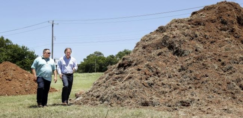 Photo -  Todd Dilbeck, left, athletic director for Oklahoma City Public Schools, and Tim McLaughlin, Fields & Futures founder, walk past a large mound of dirt in an open field behind F. D. Moon Middle School where work has begun to build athletic facilities. Fields & Futures is an Oklahoma City charity leading a campaign to renovate athletic fields at local public schools.  [Jim Beckel/The Oklahoman]