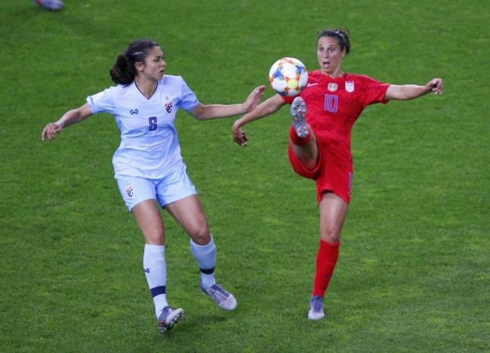 Photo -  Carli Lloyd attempts to control the ball as Thailand's Miranda Nild, left, watches during the United States' 13-0 win Tuesday in both teams' World Cup opener in Reims, France. [AP Photo/Francois Mori]