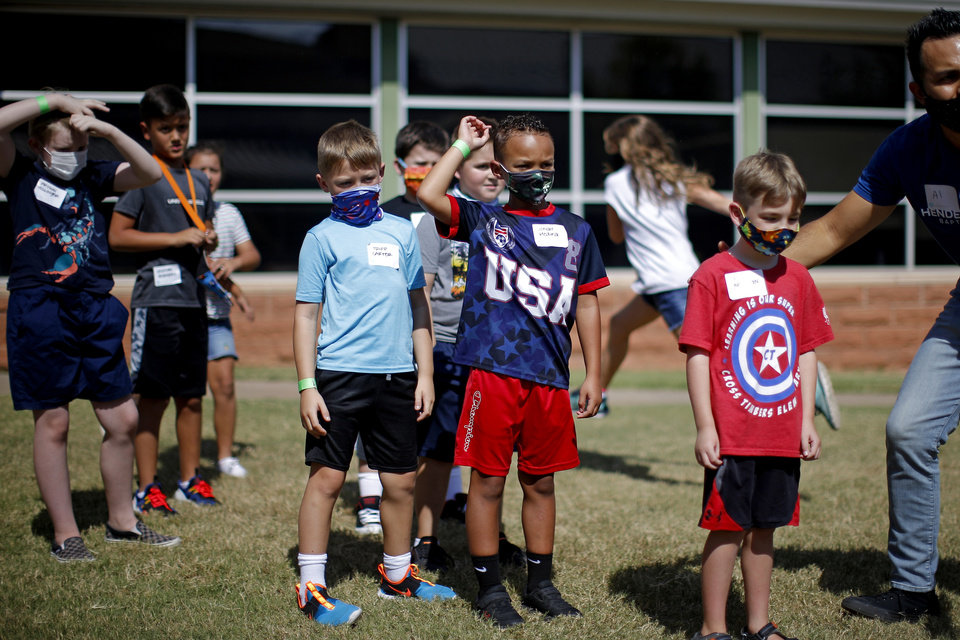 Photo - Children line up as they play a game outside Henderson Hills Baptist Church in Edmond, Okla., Wednesday, Aug. 26, 2020. The church has begun offering Edmond school students a place to go on Wednesdays to get homework help, use the free wi-fi for virtual learning, free lunch and other activities. [Bryan Terry/The Oklahoman]