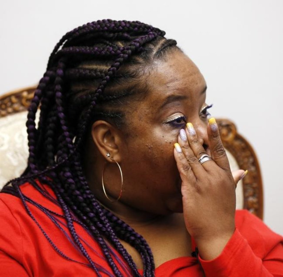 Photo -  Tondalao Hall, an Oklahoma City mother and victim of domestic violence who was sentenced to 30 years for failing to protect her children from abuse, wipes tears from her eyes during an interview Tuesday in Oklahoma City. Gov. Kevin Stitt commuted Hall's sentence last November. [Nate Billings/The Oklahoman]