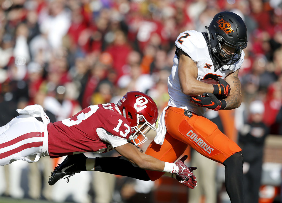 Photo - Oklahoma State's Tylan Wallace (2) gets past Oklahoma's Tre Norwood (13) after a reception in the first quarter during a Bedlam college football game between the University of Oklahoma Sooners (OU) and the Oklahoma State University Cowboys (OSU) at Gaylord Family-Oklahoma Memorial Stadium in Norman, Okla., Nov. 10, 2018.  Photo by Sarah Phipps, The Oklahoman