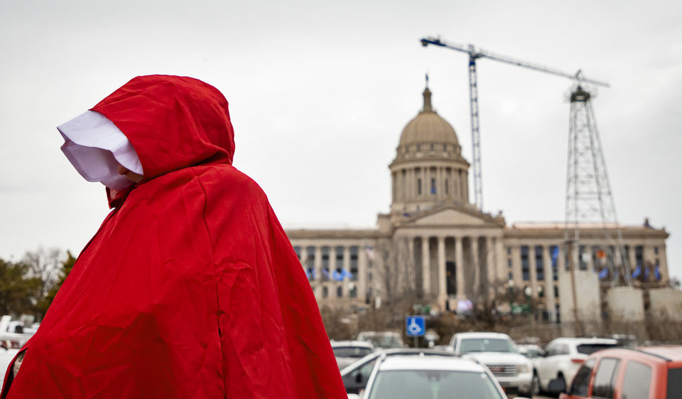 Photo - Pro-Choice supporter dressed in handmaid attire takes part in a Pro-Choice  rally against Senate Bill 13 that would abolish abortion in the state of Oklahoma at the State Capitol in Oklahoma City, Okla. on Tuesday, Feb. 11, 2020.  [Chris Landsberger/The Oklahoman]