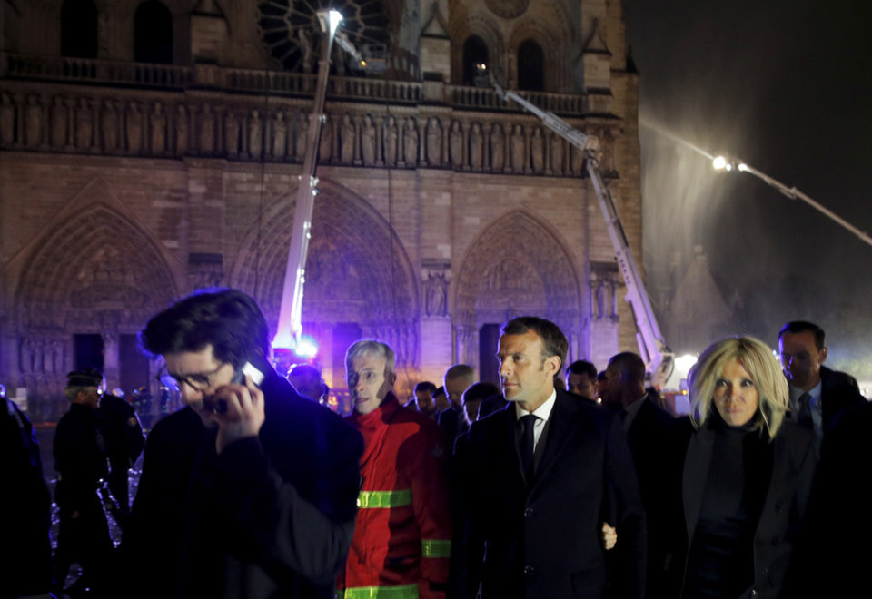 Photo - French President Emmanuel Macron, center, and his wife Brigitte walk away from Notre Dame cathedral in Paris, Monday, April 15, 2019. A catastrophic fire engulfed the upper reaches of Paris' soaring Notre Dame Cathedral as it was undergoing renovations Monday, threatening one of the greatest architectural treasures of the Western world as tourists and Parisians looked on aghast from the streets below.(Philippe Wojazer/Pool via AP)
