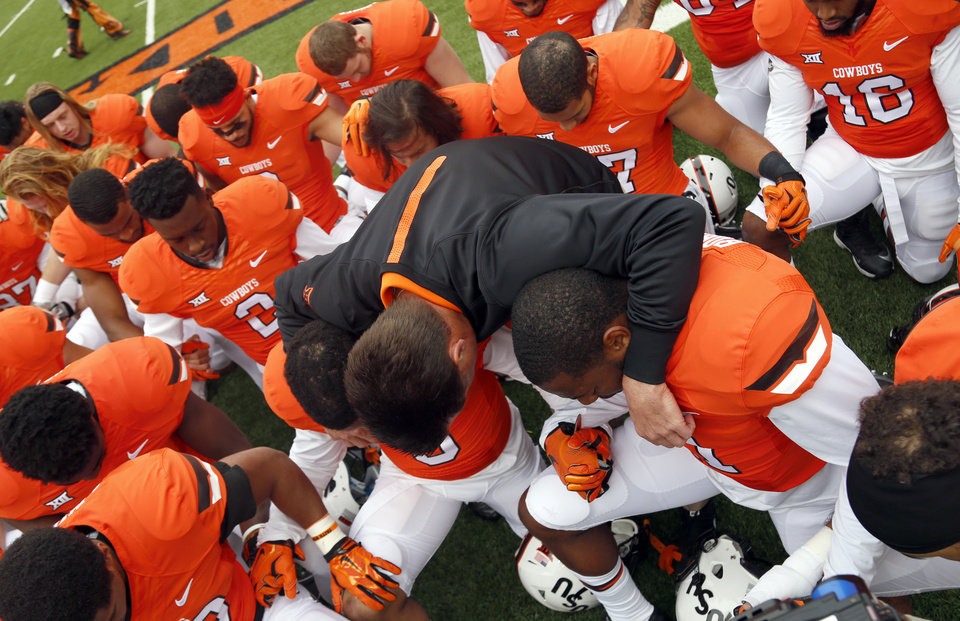 Photo - Oklahoma State head coach Mike Gundy joins the team in prayer before a college football game between the Oklahoma State University Cowboys (OSU) and the Kansas Jayhawks (KU) at Boone Pickens Stadium in Stillwater, Okla., Saturday, Oct. 24, 2015. Photo by Sarah Phipps, The Oklahoman