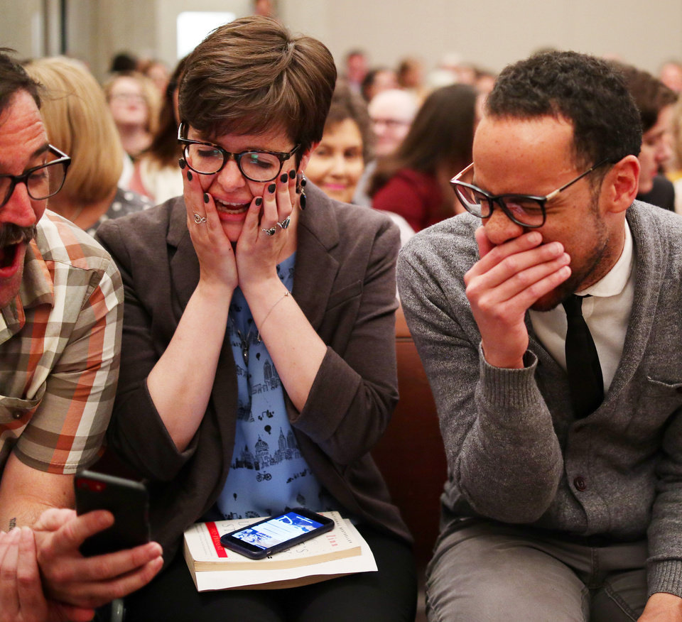 Photo - JoBeth Hamon and James Cooper react to something on Marty Peercy's phone before the swearing in ceremony for the Oklahoma City Council, Tuesday, April 9, 2019.  Photo by Doug Hoke/The Oklahoman