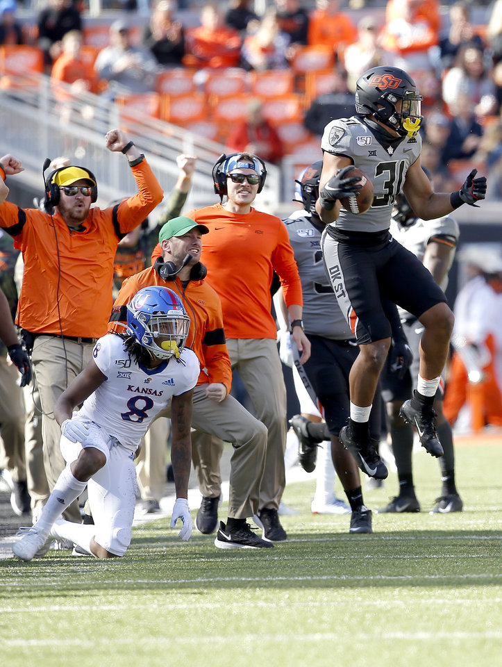 Photo - Kolby Harvell-Peel (31) celebrates an interception next to  Kansas's Kwamie Lassiter II (8) in the second quarter during the college football game between the Oklahoma State University Cowboys and the Kansas Jayhawks at Boone Pickens Stadium in Stillwater, Okla., Saturday, Nov. 16, 2019. OSU won 31-13. [Sarah Phipps/The Oklahoman]
