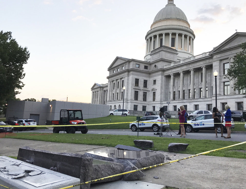 Photo - The new Ten Commandments monument outside the state Capitol in Little Rock, Ark., is blocked off Wednesday morning, June 28, 2017, after someone crashed into it with a vehicle, less than 24 hours after the privately funded monument was placed on the Capitol grounds. Authorities arrested a male suspect. (AP Photo/Jill Zeman Bleed)