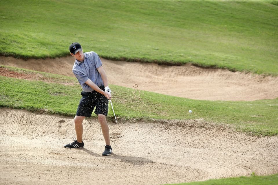 Photo - Sutton McMillan, Choctaw High School golfer, hits out of a sand trap, onto the 18th green, during Class 6A boys golf state tournament at Rose Creek golf course on Monday, May 6, 2019.  [Jim Beckel/The Oklahoman]
