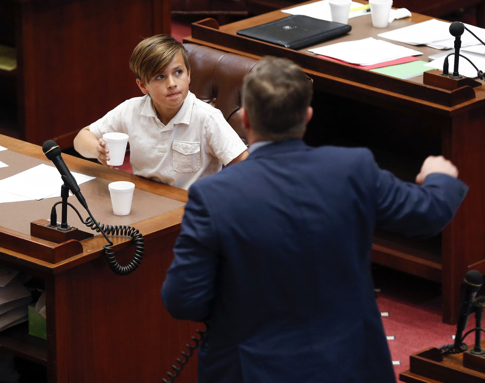 Photo - Mason Treat listens to his father, State Sen. Greg Treat, speak about special session House Bill 1019XX during the fifth day of a walkout by Oklahoma teachers at the state Capitol in Oklahoma City, Friday, April 6, 2018. Photo by Nate Billings, The Oklahoman