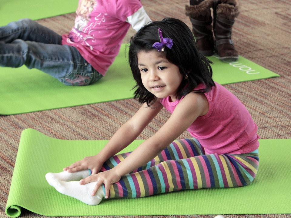 Photo - Above: Adilene Soto does a pose as Angela Moorad teaches yoga to 3- and 4-year-olds Wednesday.