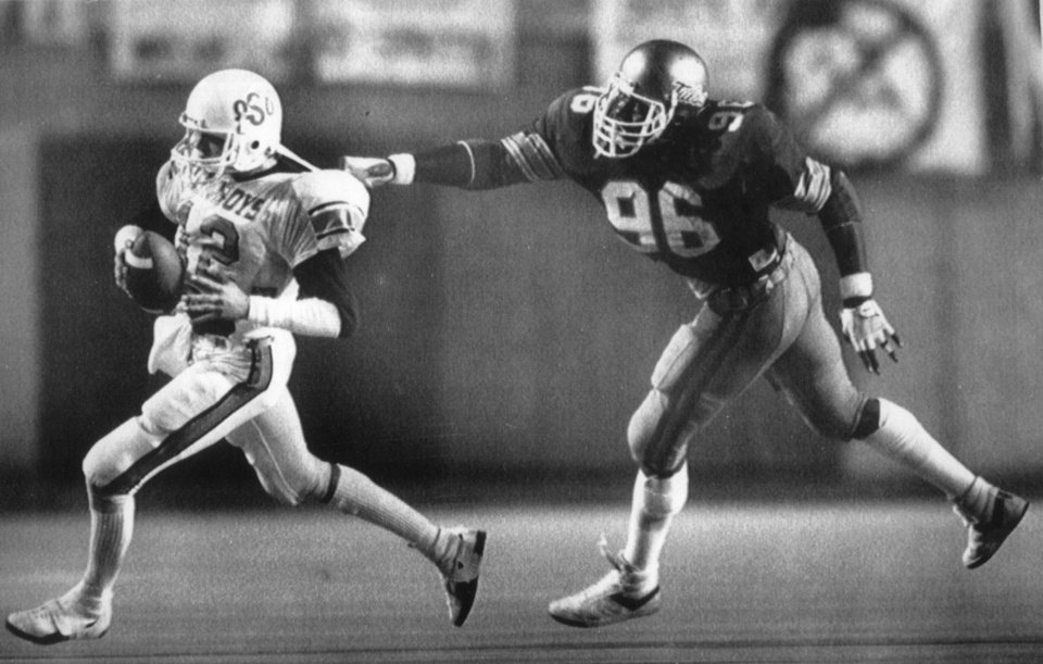 Photo - COWBOYS /  OKLAHOMA STATE UNIVERSITY, COLLEGE FOOTBALL, OSU: 9/29/1984-OSU's Rusty Hilger tries to pull away from Tulsa's Brian Bruner. Staff photo by Doug Hoke.