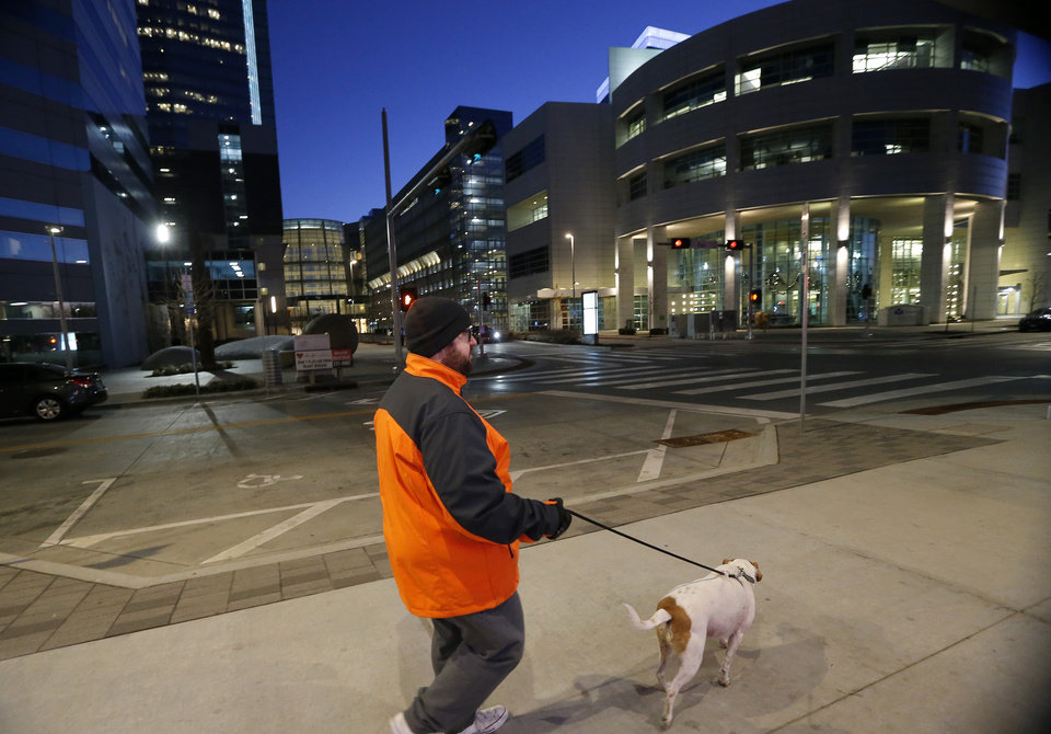 Photo -  Cody Lusnia walks his dog, Rip, in downtown Oklahoma City. Lusnia has brought attention to an issue involving nonworking street/sidewalk lights using social media. [The Oklahoman archives]