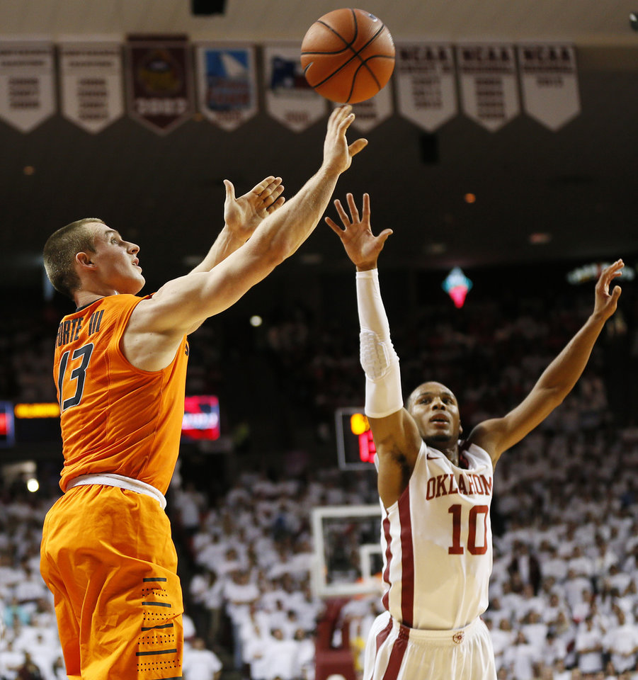 Photo - Oklahoma State's Phil Forte (13) shoots against Oklahoma's Jordan Woodard (10) in the first half during the NCAA men's Bedlam basketball game between the Oklahoma State Cowboys (OSU) and the Oklahoma Sooners (OU) at Lloyd Noble Center in Norman, Okla., Monday, Jan. 27, 2014. Photo by Nate Billings, The Oklahoman