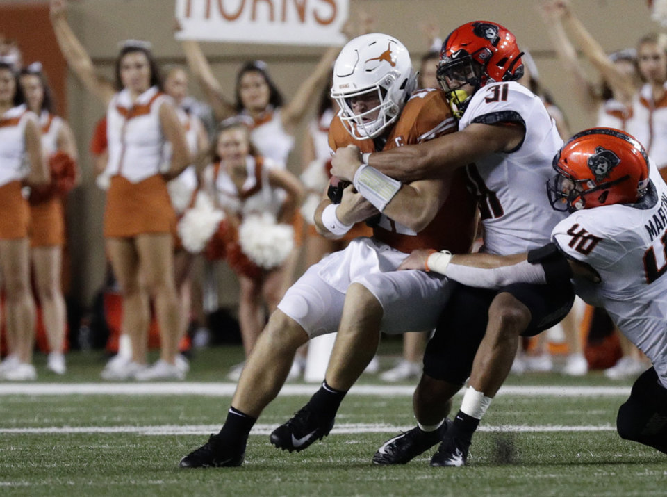 Photo - Texas quarterback Sam Ehlinger (11) is stopped by Oklahoma State safety Kolby Harvell-Peel (31) and Oklahoma State defensive end Brock Martin (40) during the second half of an NCAA college football game Saturday, Sept. 21, 2019, in Austin, Texas. (AP Photo/Eric Gay)