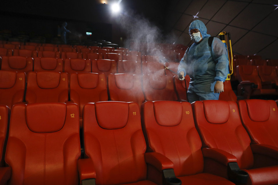 Photo -  A staff member of a cinema sprays disinfectant at the cinema hall to prepare for reopening on July 1 in Kuala Lumpur, Malaysia, Friday, June 26, 2020. Malaysia entered the Recovery Movement Control Order (RMCO) after three months of coronavirus restrictions. (AP Photo/Vincent Thian)