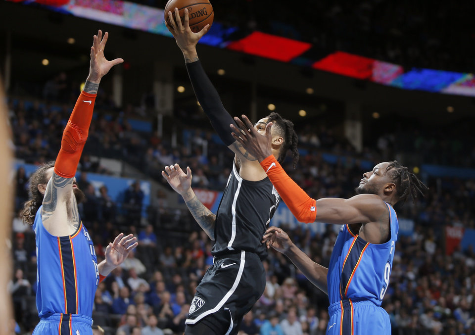 Photo - D'Angelo Russell (1) goes to the basket between Oklahoma City's Steven Adams (12)  and Jerami Grant (9) during an NBA basketball game between the Oklahoma City Thunder and the Brooklyn Nets at Chesapeake Energy Arena in Oklahoma City, Wednesday, March 13, 2019. Photo by Bryan Terry, The Oklahoman