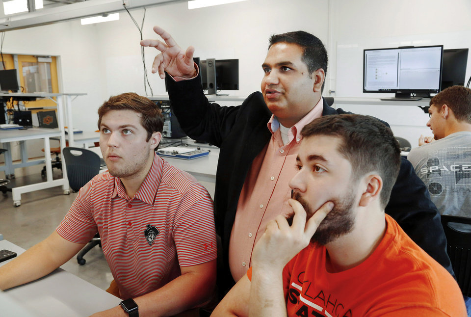 Photo -  Seniors Matthew Anderson, left, and Thomas Meadows, right, receive guidance from assistant professor Hitesh Vora while they complete an assignment in Endeavor's mechanical engineering technology lab. [Photo by Jim Beckel, The Oklahoman]