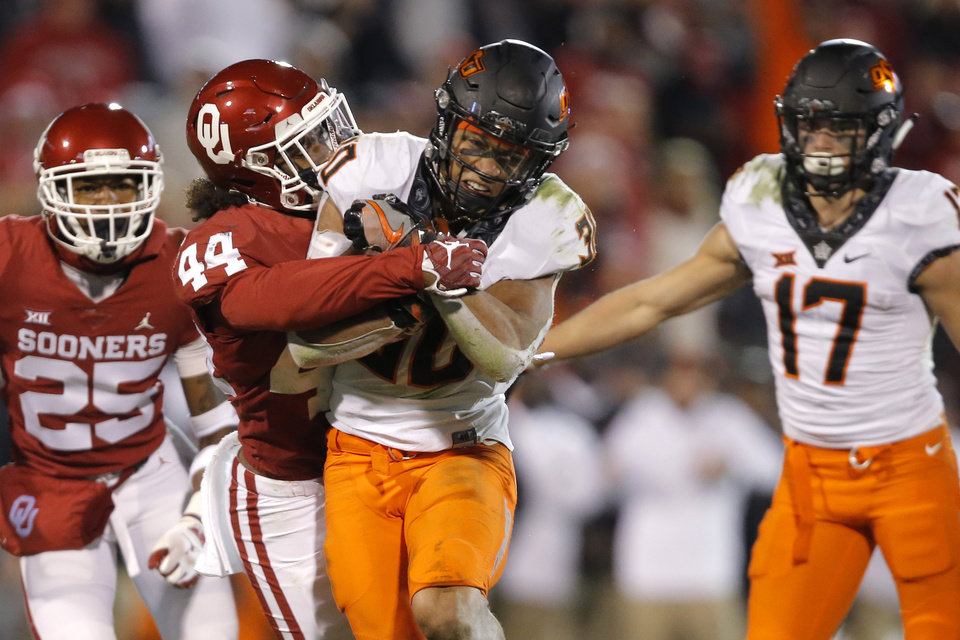 Photo - Oklahoma State's Chuba Hubbard (30) is brought down by Oklahoma's Brendan Radley-Hiles (44) during a Bedlam college football game between the University of Oklahoma Sooners (OU) and the Oklahoma State University Cowboys (OSU) at Gaylord Family-Oklahoma Memorial Stadium in Norman, Okla., Nov. 10, 2018.  Photo by Bryan Terry, The Oklahoman