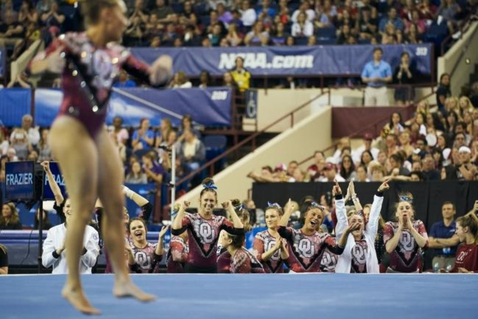 Photo -  Oklahoma celebrates after teammate's Olivia Trautman's floor routine during the NCAA college women's gymnastics championship, Saturday, April 20, 2019, in Fort Worth, Texas. (AP Photo/Cooper Neill)