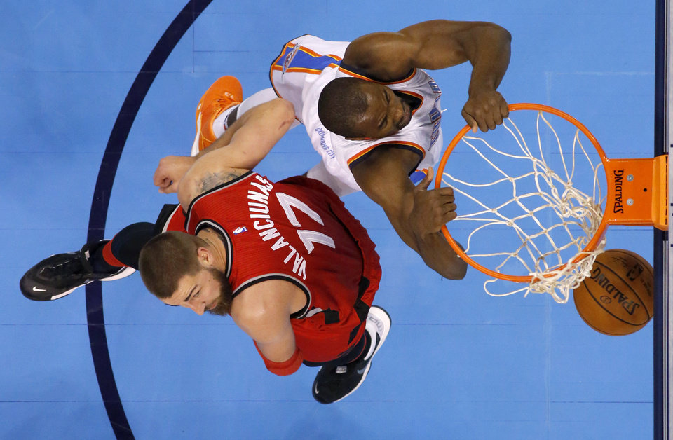 Photo - Oklahoma City's Serge Ibaka (9) dunks the ball in front of Toronto's Jonas Valanciunas (17) during an NBA basketball game between the Oklahoma City Thunder and the Toronto Raptors at Chesapeake Energy Arena on Wednesday, Nov. 4, 2015. Photo by Bryan Terry, The Oklahoman