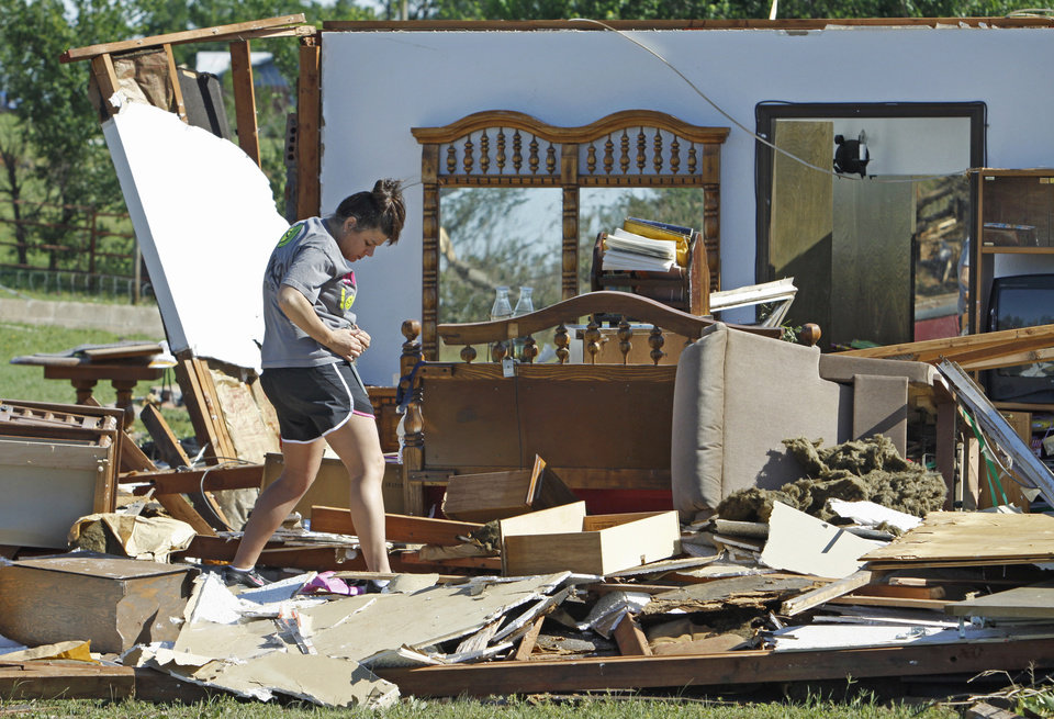 Photo - Kristi McDaniel-Edwards looks for items at the home of her grandmother Louise McDaniel's as residents cleanup following Tuesday's deadly tornado on Wednesday, May 25, 2011, in Chickasha, Okla.  Louise was with her hospitalized son Ronnie McDaniel in Oklahoma City when the tornado destroyed her home.  Louise McDaniel saw the destruction and recognized her yard from aerial television coverage. Photo by Steve Sisney, The Oklahoman