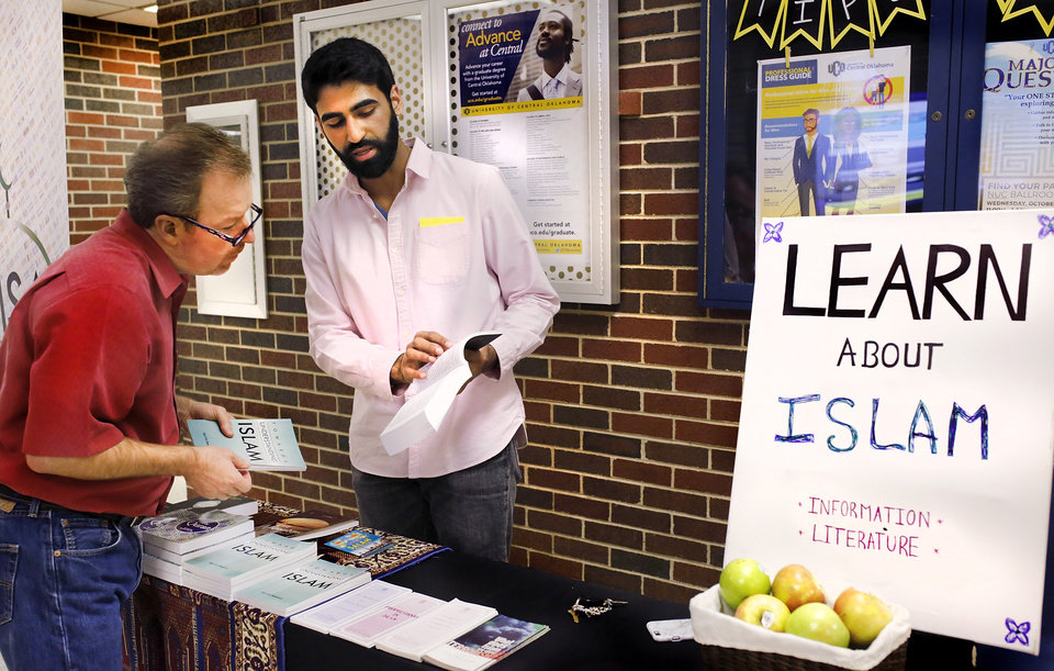 Photo -  Umar Sahi, a student at the University of Central Oklahoma, discusses Islam with visitors at an informational booth in the Nigh University Center. [Photo by Jim Beckel, The Oklahoman]