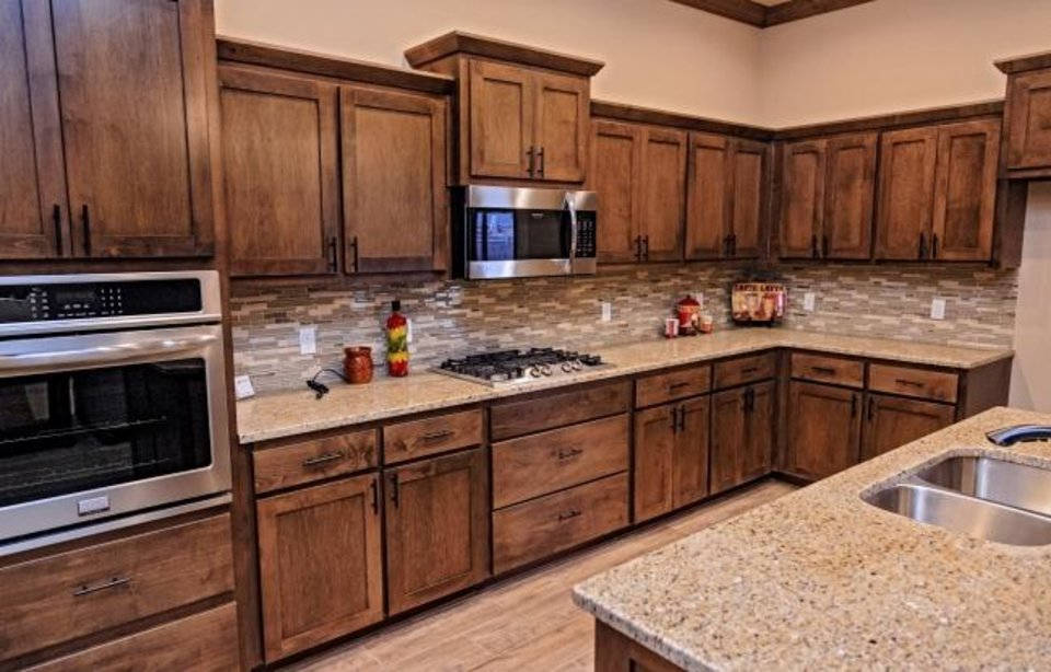 Photo -  Dark stain featured in the Vesta Homes model at 12801 Williamson Farm Blvd. Builder Jim Schuff says this was a model home for two years as tastes changed. The trend is for less cabinetry in kitchens, he says. [CHRIS LANDSBERGER/THE OKLAHOMAN]